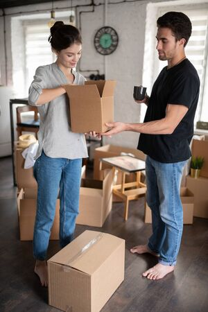 Couple unpacking cardboard boxes in cozy room