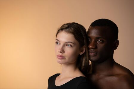 Affectionate multiethnic couple standing one after another at studio