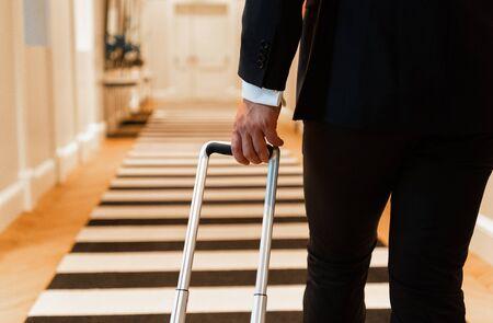 Crop businessman walking in hotel corridor