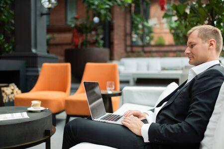 Confident entrepreneur browsing laptop on hotel terrace