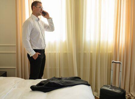 Adult businessman talking on phone in hotel 写真素材