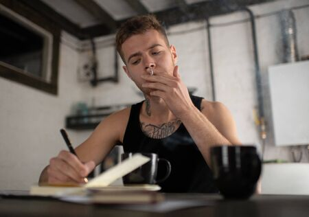 Concentrated hipster songwriter smoking cigarette while working at home Foto de archivo