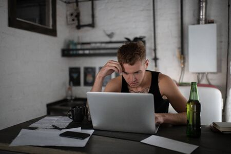 Concentrated freelancer browsing laptop