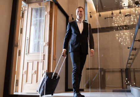 Adult businessman entering luxury hotel during business trip 写真素材
