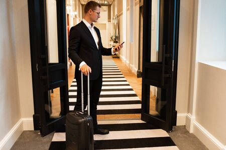 Businessman using smartphone in hotel corridor