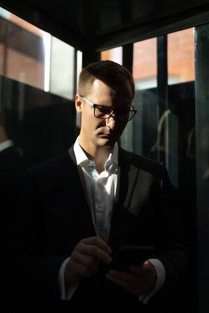Entrepreneur using smartphone in elevator during business trip