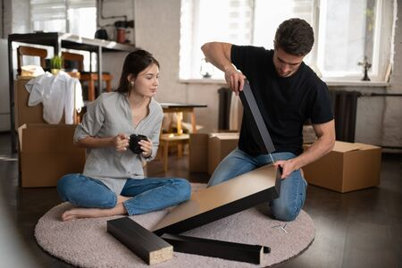 Young woman watching boyfriend assembling table during relocation
