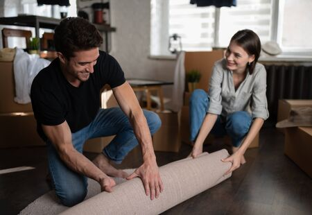 Optimistic couple with rolled carpet in new apartment