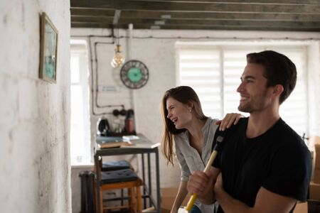 Cheerful couple admiring picture on wall during relocation 写真素材