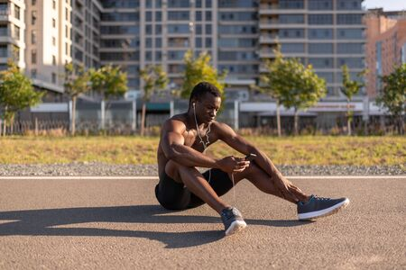 Black athletic male listening to music through earphones and smartphone