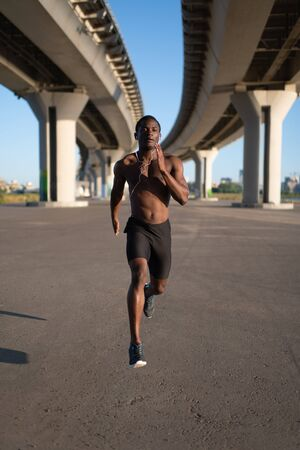 African American male running fast on track 写真素材