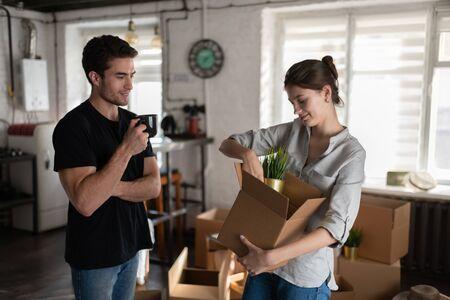 Couple unpacking belongings in cozy room during relocation 写真素材