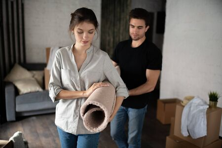 Woman carrying carpet with boyfriend during relocation 写真素材