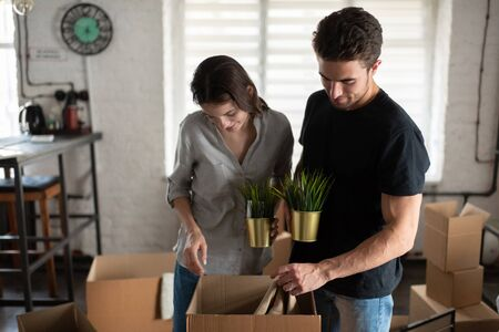 Couple examining belongings in carton box during relocation