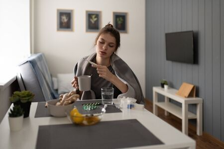 Diseased woman drinking tea and measuring temperature