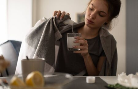 Young woman pouring medicine into the glass 写真素材