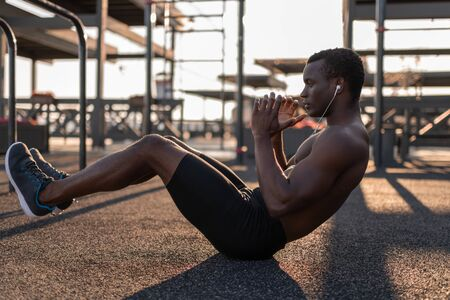 Fit black man doing abs exercises while listening to music in earphones