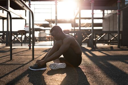 Strong black man tying sneaker on playground 写真素材