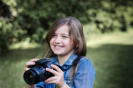 photocamera: Happy beautiful little girl with photocamera, summer portrait. Stock Photo