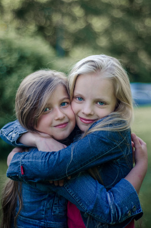 blond haired: Brown and blond haired cute little girls friends smiling and hug Stock Photo