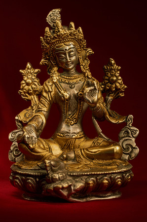 tare: Statuette of Green Tara on a red background. Vajrayana deity, quick to help and protection. Om tare tuttare ture soha.