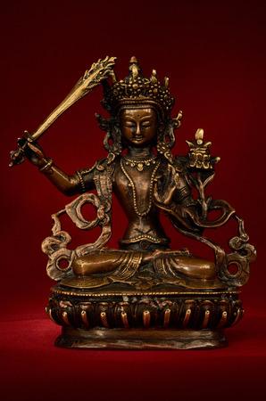 transcendent: Statuette of Manjushri brandishing sword of wisdom on a red background. Manjushri, Still a Youth. Vajrayana deity.