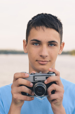 rangefinder: Cute boy teenager with vintage rangefinder camera. Close-up Photo.