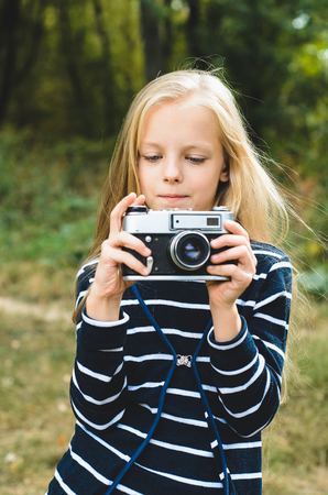 handheld device: Cute little girl with a vintage rangefinder camera. Beautiful long blond hair.