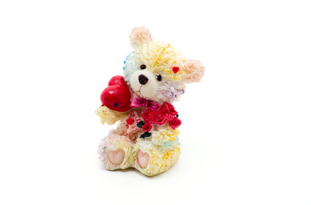 bear s: Statuette of a little bear with red heart and flowers isolated on a white background.