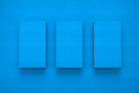 Mockup of three vertical business cards on blue textured paper studio. High resolution 3d render.