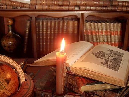 Burning candle, ancient books and globe.