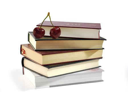 Pile of books and two sweet cherries isolated over white. photo
