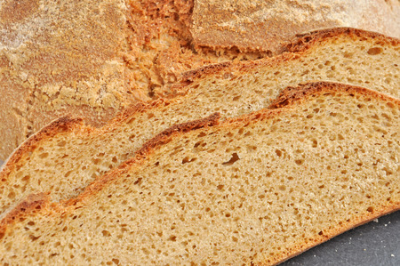 wholegrain: Sliced home-baked bread made using Natural Starter and organic wholegrain wheat flour on a black slate plate tray. Healthy food concept.