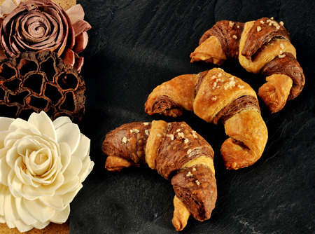 bicolored: Three bicolored croissant served on black slate plate tray with decorations made of natural material. Stock Photo