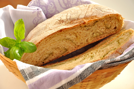 sprig: Sliced wheat bread with pesto and sprig of basil in the basket. Healthy food concept. Stock Photo