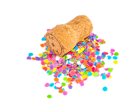 corkwood: Champagne cork lying on the small heap of confetti: isolated over white. Holidays and events concept.