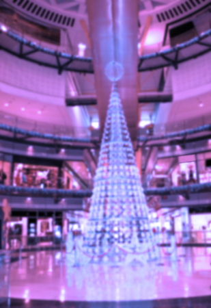 multilevel: Blurred Christmas background: exquisite Christmas and New Year decorations and shining Christmas tree in multilevel shopping mall.