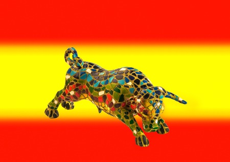 spanish bull: Miniature multicolored statue of bull in Gaudi style on background of colors of spanish flag. This is not art object, only  traditional souvenir from Barcelona Spain.