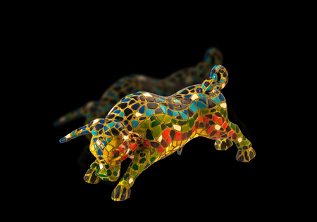 souvenir traditional: Miniature multicolored statue of bull in Gaudi style on black background with reflection. This is not art object, only traditional souvenir from Barcelona Spain.