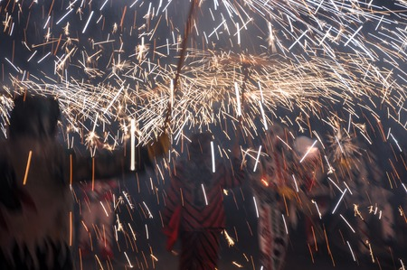 treading: Traditional correfocs (fire runs) performance (Spanish: Baile de Diablos, Catalan: Ball de Diables or Correfocs). Group of people dressed as devils and treading the streets letting off fireworks. Stock Photo