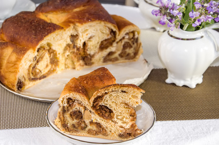 Good piece of typical italian flavorous home baked cake La Gubana with sophisticated stuffing (hazelnuts, fruit, chocolate, walnut, raisins, honey etc.) with purple flowers of salvia. Traditionally bake for Christmas and Easter.