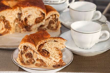 Good piece of typical italian flavorous home baked cake La Gubana with sophisticated stuffing (hazelnuts, fruit, chocolate, walnut, raisins, honey etc.) on the table covered for tea time. Traditionally bake for Christmas and Easter. Stock Photo