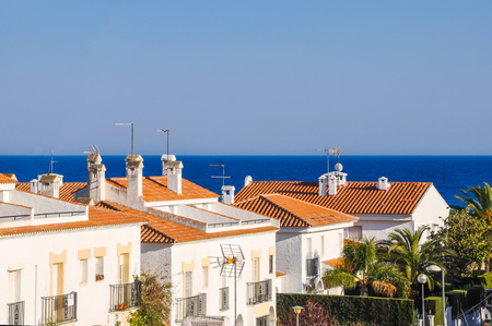 snug: Small mediterranean snug resort town on Costa Dorada, Spain. Chalets beside the sea. Summer vacations concept. Horizontal.