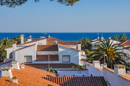 Sea view atop of terracotta tiles roofs. Travel destination. Summer vacations concept. Costa Dorada, Spain. Horizontal.