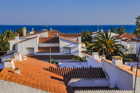 View on housetops  from terracotta tiles, palm trees, blue sea. Travel destination. Costa Dorada, Spain. Horizontal.