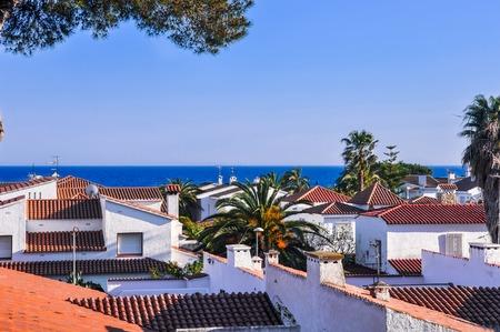 Roofs from terracotta tiles, palm trees, the sea on horizon. Travel destination. Costa Dorada, Spain. Horizontal. Stock Photo
