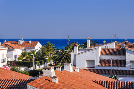 Roofs from terracotta tiles, palm trees, blue sea. Travel destination. Costa Dorada, Spain. Horizontal. Stock Photo