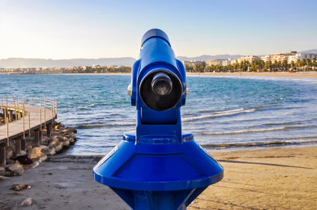 seafronts: Pay telescope overlooking beach and seafront of maritime city with sea, buildings and silhouette of mountains in the background. Costa Dorada, Spain. Horizontal. Stock Photo