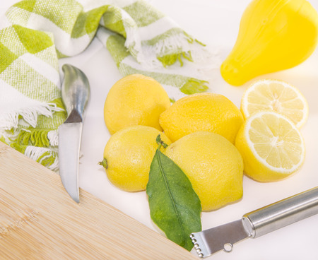 gratings: Juicy lemons, silicon squeezer, knife, Zester and wooden cutting board on the table.