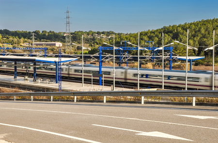 Modern high speed train departs from railway station with natural motion blur effect and beautiful landscape. Camp de Tarragona, Spain. Horizontal. Stock Photo